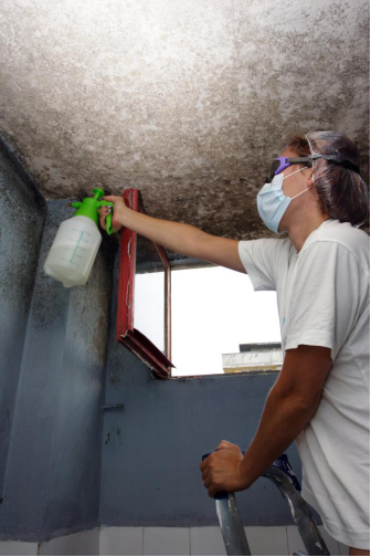 A woman wearing safety goggles and a face mask inspects mold growing on a wall